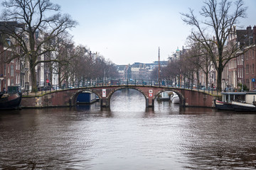 water canals in Amsterdam with a bridge in the middle and buildings on both of bridge's side