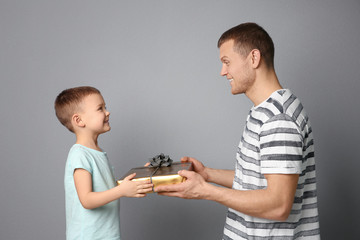Man receiving gift for Father's Day from his son on grey background