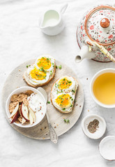 Morning breakfast table inspiration - sandwiches with cream cheese and boiled egg, yogurt with apple and flax seeds, herbal detox tea on light background, top view. Flat lay