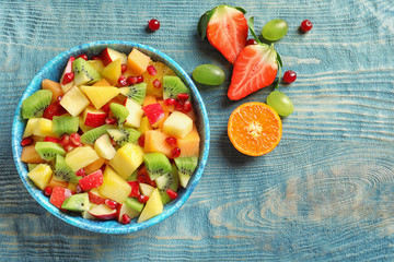 Bowl with fresh cut fruits on wooden table, top view