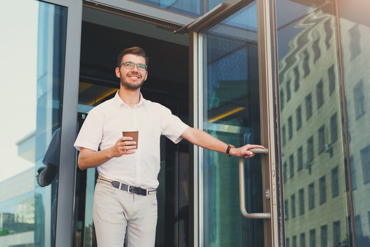 Happy smiling businessman with coffee leaving the building