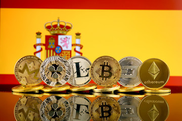 Physical version of Cryptocurrencies (Monero, Ripple, Litecoin, Bitcoin, Dash, Ethereum) and Spain Flag.