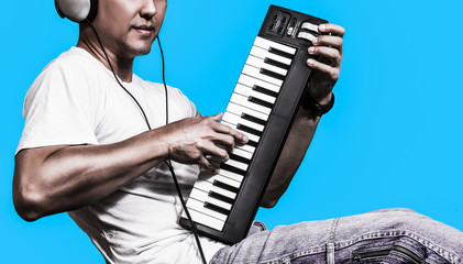 man listening music & playing midi keyboard, isolated on blue