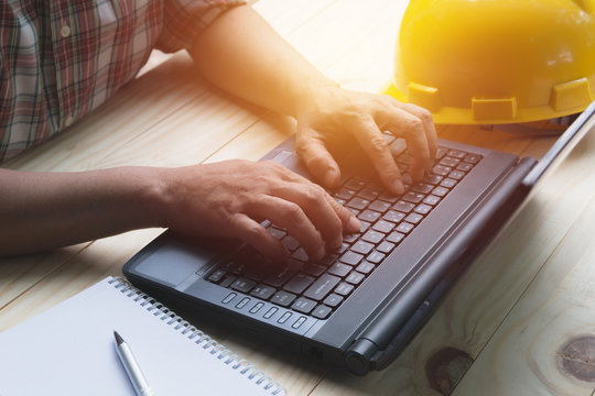 Architect engineer using laptop for working with yellow helmet on table.