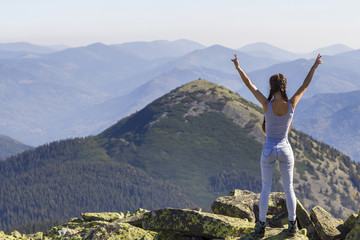 Silhouette of a young happy beautiful slim girl with long braids standing on big rocks in mountains lifting hands, meeting a raising sun. Tourism and traveling.