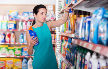 Woman choosing detergent for washing