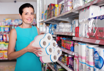 Smiling woman choosing pack of toilet paper