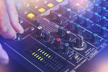 Hand with audio mixing board