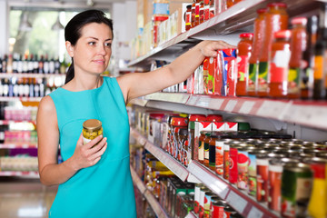 Woman readig label on jar of tomato sauce
