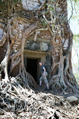 the woman at an entrance to the destroyed covered with roots of trees temple Prasat Chrap in the Koh Ker temple complex, Siem Reap, Cambodia..