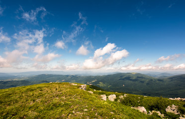 beautiful mountainous landscape in summer. lovely nature scenery observed from the top of a hill with giant boulders. fine weather with blue sky and some fluffy clouds