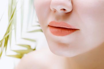 Orange lips. Female face closeup.