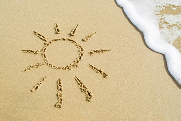 Drawing sun on beach - vacation concept background