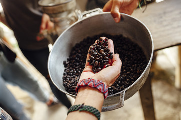 Hand of a woman showing roasted coffee beans from a pot