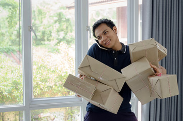 handsome young asian delivery man happy after new order from customer and lifting many packaging parcel box with mobile phone in home office, small business owner, cargo, mail, and shipping concept