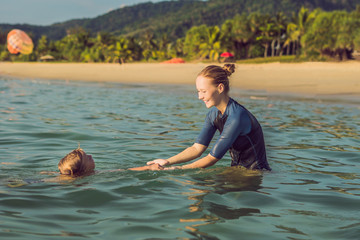 Woman swimming instructor for children is teaching a happy boy to swim in the sea