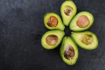 ripe sliced avocado on dark  background, top view