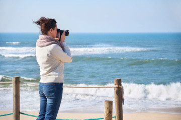 Young woman taking photos at a beach