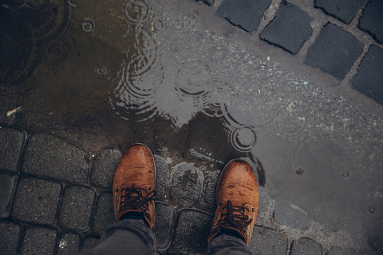 mans legs next to puddle. rainy weather.