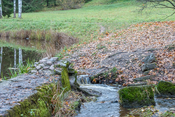 Small creek and lake in autumn park