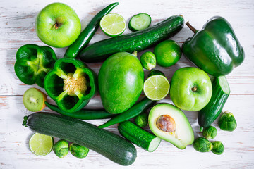 green vegetables and fruits on white wooden background sliced for half. slides . overhead view