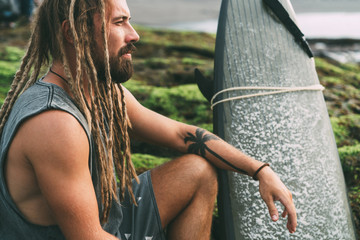 Surfer with dreadlocks and tatoos with surfingboard