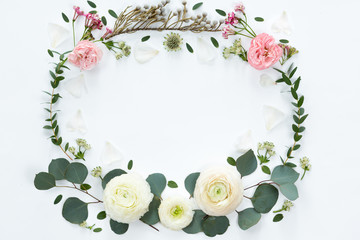 FLower frame with fresh branches of pion-shaped roses and eucalyptus leaves isolated on white background, flat lay and top view