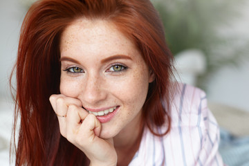 Picture of charming young female with loose red hair and freckles lying on bed at home, keeping hand under her chin and looking at camera with happy positive smile, posing against blurred background