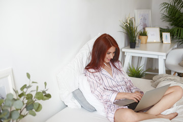 Candid shot of charming positive young redhead female in pajamas sitting cross legged on undone bed with notebook pc on her lap, using earphone, listening to music and chatting with friends online