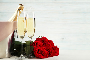 Champagne bottle with glasses and bouquet of red roses on wooden table