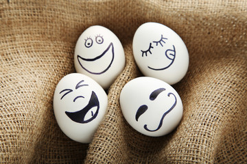 Eggs with funny faces on brown sackcloth