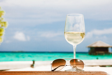 glass of chilled white wine and sunglasses on table on a tropical background