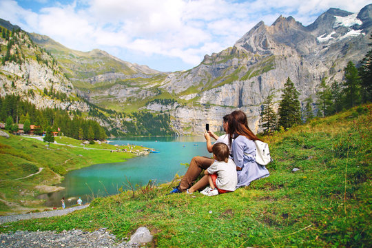 young happy family of tourists photographing nature, beautiful blue natural lake oeschinensee, in Switzerland, a fantastic mountain landscape overlooking the water and forest
