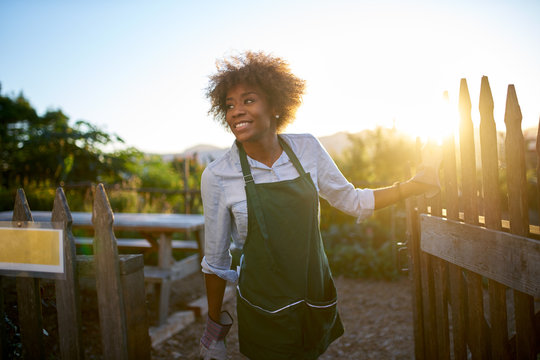 african american female gardener walking out of community urban garden at end of day