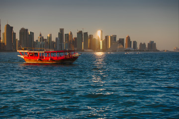 A traditional wooden Dhow cruising with the skyline of West Bay in background, seen at sunset from the Dhow Harbour. Doha, Qatar.
