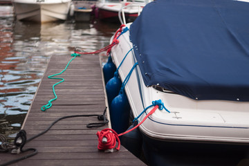 a modern motor boat windshield and bow deck covered in a blue canvas rain cover, with a weathered wood dock and blurry port in background Wall mural