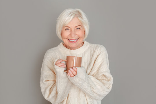 Senior woman in sweater studio isolated on grey wall drinking hot chocolate