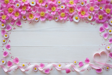 Wooden background with pink flowers, roses, daisies and ribbon