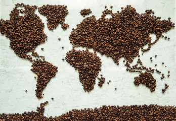The world map from coffee beans on a light concrete background