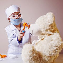 Girl playing doctor and treats teddy bear (Health, medicine, hospital, veterinary medicine concept)