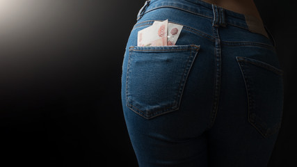 Money in the back pocket of the girl's jeans. On a black background, with an empty space for inscription or advertising.