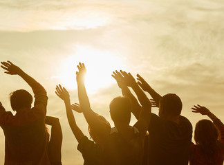Silhouettes of happy people with hands up. Warming-up before sport exercises.