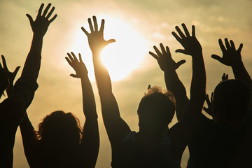 Dancing people at rock concert. Young people with hands up looking at the sun while sunset.