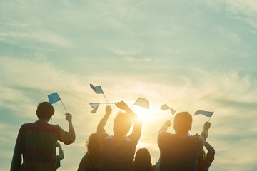 People raising european union flags in the air. Family facing the sun and waving small euro flags, back view.