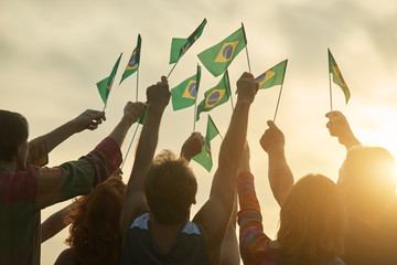 Rising up brazil flags. Crowd of people holding brazilian flags, back view. Wall mural