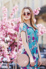 Outdoor portrait of young beautiful girl with small round pink bag, wearing stylish sunglasses, blue dress. Model posing in street, blooming trees on background. City lifestyle. Female fashion concept