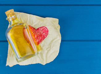 The red heart is painted on paper. On it there is an elixir in a small bottle.