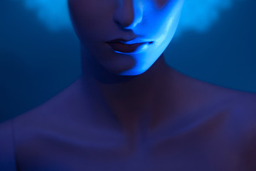 Lips of a woman. Mannequin on a blue background. Part of a woman's face.