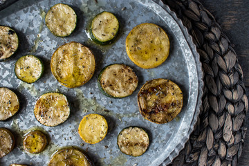 grilled sliced summer squash with olive oil and herbs in rustic setting