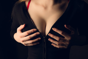 Sexy woman tits in black jacket. Woman zip up black jacket. Woman hands take zip lock of black sweater. Sexy tits in push-up bra